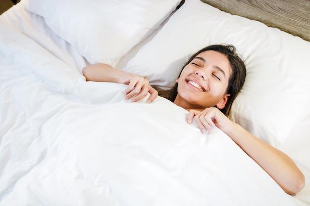 Rozochocona młoda kobieta ono uśmiecha się i zakrywa z koc w łóżku z białymi czystymi prześcieradłami. wygodny materac