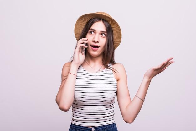 Rozochocona młoda kobieta opowiada na telefonie komórkowym odizolowywającym na szarym tle w kapeluszu