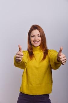 Rozochocona młoda kobieta pokazuje aprobaty
