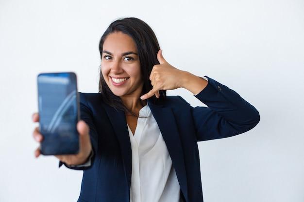 Rozochocona młoda kobieta pokazuje smartphone