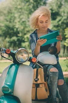 Rozochocona młoda kobieta siedzi na hulajnoga i używa cyfrową pastylkę.
