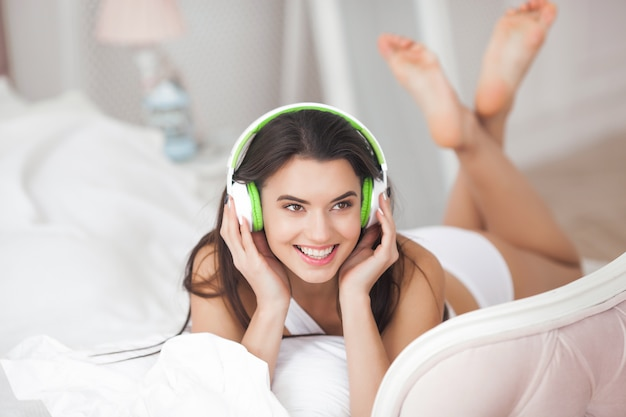 Rozochocona młoda kobieta słucha muzyka. piękna dziewczyna jest ubranym słuchawki
