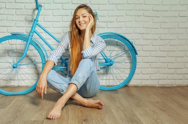 Rozochocona młoda kobieta stoi blisko bicyklu