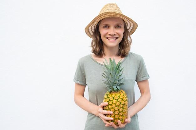 Rozochocona młoda kobieta trzyma całego ananasa w słomianym kapeluszu
