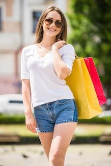 Rozochocona młoda kobieta w okularach przeciwsłonecznych z dwa torba na zakupy
