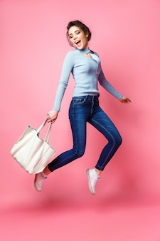 Rozochocona młoda kobieta z torebki doskakiwaniem