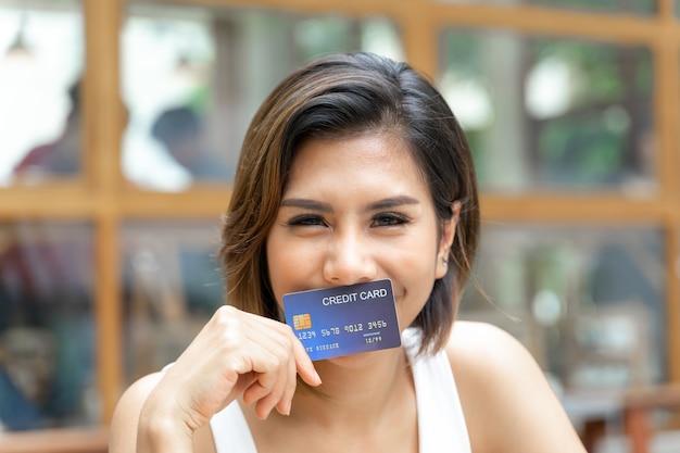 Rozochocona młoda ładna kobieta używał cradit kartę