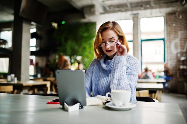 Rozochocona młoda piękna redhaired kobieta w szkłach używać jej telefon, touchpad i notatnika, podczas gdy siedzący przy jej pracującym miejscem na kawiarni z filiżanką kawy.