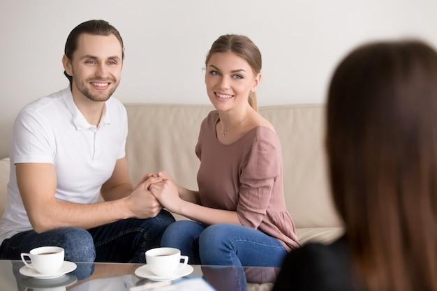 Rozochocona młoda rodzinna para na konsultaci. trzymając się za ręce i uśmiechając się