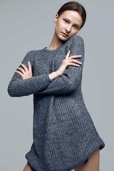 Rozochocona moda modnisia dziewczyna w wygodnym pulowerze na pracownianym tle