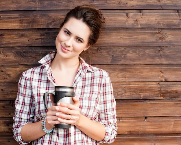Rozochocona modna kobieta trzyma kawę outdoors na drewnianym tle