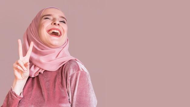 Rozochocona muzułmańska kobieta gestykuluje pokoju znaka nad pracownianym tłem