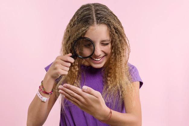 Rozochocona nastoletnia dziewczyna patrzeje przez powiększać - szkło.
