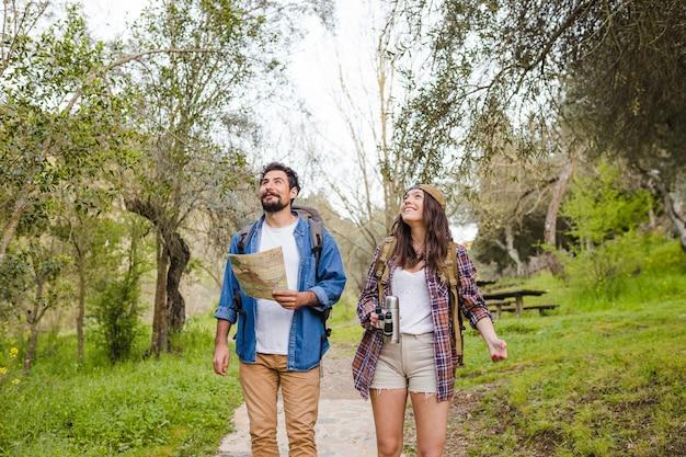 Rozochocona para podróżuje w lesie z mapą