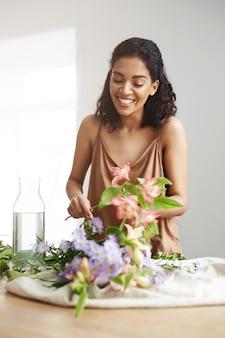 Rozochocona piękna afrykańska kwiaciarnia ono uśmiecha się robić bukietowi przy miejscem pracy nad biel ścianą.