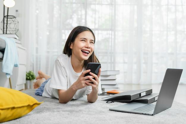 Rozochocona piękna azjatycka kobieta trzyma smartphone z laptopem i używa online ogólnospołecznych środki na stylu życia w domu. technologia koncepcji komunikacji.