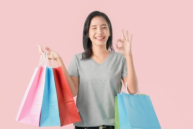 Rozochocona piękna azjatycka kobieta trzyma wielo- barwionych torba na zakupy i pokazuje ok znaka