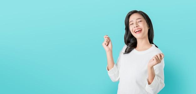 Rozochocona piękna azjatycka kobieta w przypadkowej białej koszulce i szczęśliwa twarz uśmiechamy się na błękitnym tle