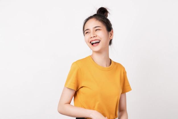 Rozochocona piękna azjatycka kobieta w żółtej koszula i stojak na biel ścianie