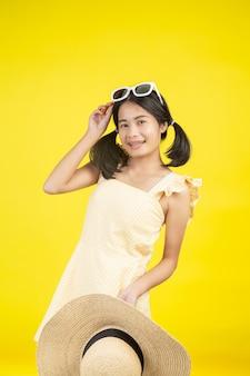 Rozochocona piękna kobieta jest ubranym dużego kapelusz z białymi szkłami na kolorze żółtym.