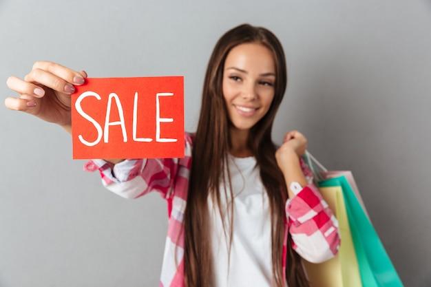 Rozochocona piękna kobieta pokazuje sprzedaż znaka i trzyma torba na zakupy