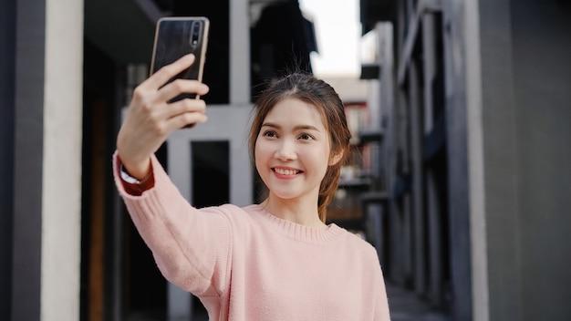 Rozochocona piękna młoda azjatycka backpacker blogger kobieta używa smartphone bierze selfie podczas gdy podróżujący przy chinatown w pekin, chiny.