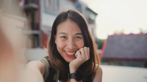 Rozochocona piękna młoda azjatycka backpacker blogger kobieta używa smartphone bierze selfie