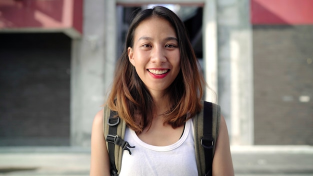Rozochocona piękna młoda azjatycka backpacker kobieta czuje szczęśliwego ono uśmiecha się kamera