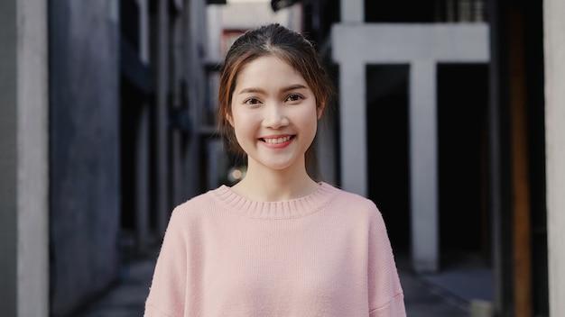 Rozochocona piękna młoda azjatycka kobieta czuje szczęśliwy ono uśmiecha się kamera podczas gdy podróżujący przy chinatown w pekin, chiny.