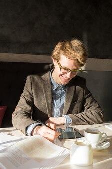 Rozochocona przystojna samiec uśmiecha się czytelniczego pastylka komputer osobistego przy kawiarnią na lunch.