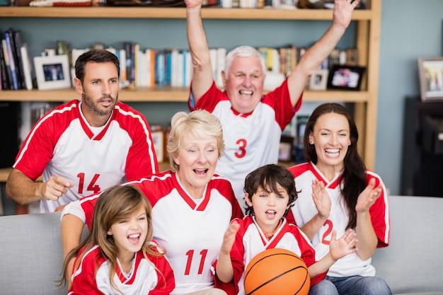 Rozochocona rodzina z dziadkami ogląda mecz koszykówki
