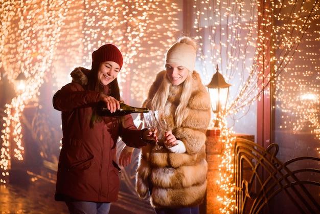 Rozochocona roześmiana kobieta świętuje przyjęcia z szampanem.