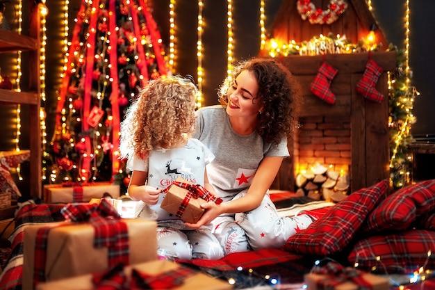 Rozochocona śliczna mała dziewczynka i jej starsza siostra wymienia prezenty.