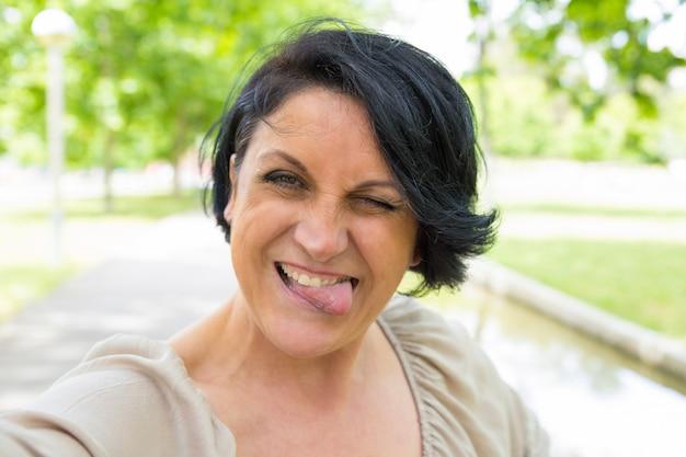 Rozochocona śmieszna kobieta skrzywi się selfie i bierze