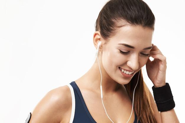 Rozochocona sportive sprawności fizycznej kobieta ono uśmiecha się patrzeć w dół na bielu w słuchawkach.