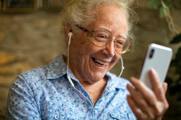 Rozochocona starsza kobieta robi wideo wezwaniu