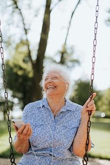 Rozochocona starsza kobieta słucha muzyka przy boiskiem