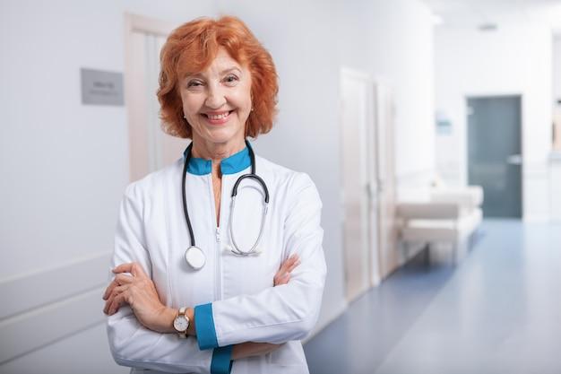 Rozochocona starsza kobiety lekarka ono uśmiecha się kamera