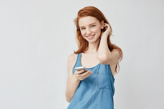 Rozochocona szczera lisica dziewczyna z piegami uśmiecha się mienie telefon.