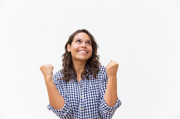 Rozochocona szczęśliwa kobieta robi zwycięzcy gestowi i przyglądającemu up