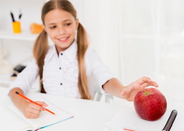 Rozochocona uczennica uśmiecha się czerwonego jabłka i bierze