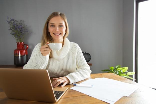 Rozochocona ufna młoda kobieta używa laptop i pijący kawę