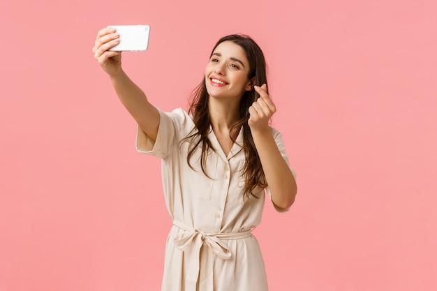 Rozochocona urocza młoda europejska kobieta używa filtr, aby wziąć ślicznego selfie, fotografuje na mobilnym aparacie, uśmiecha się i pokazuje koreańskiego gest serca na smartfonie, stoi różowy