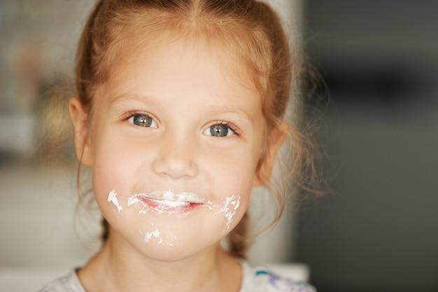 Rozochocona uśmiechnięta dziecko dziewczyna je wyśmienicie tort i pokazuje aprobaty. usta w śmietanie. wesołe beztroskie dzieciństwo