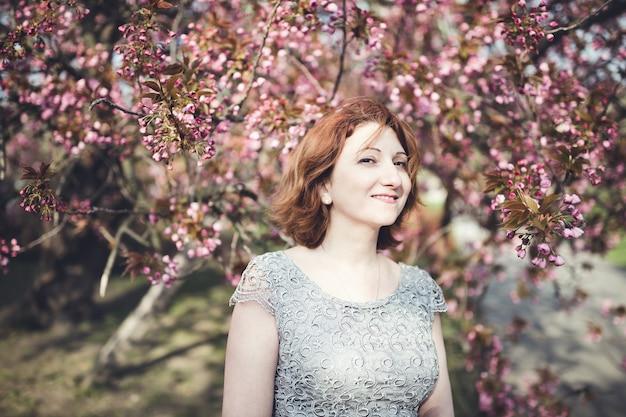 Rozochocona w średnim wieku armeńska kobieta w eleganckiej sukni pod kwitnącym sakura drzewem.