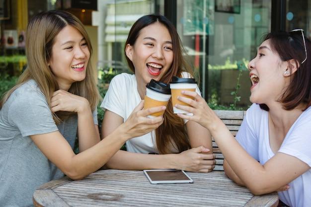 Rozochocone azjatykcie młode kobiety siedzi w kawiarni pije kawę z przyjaciółmi i opowiada wpólnie