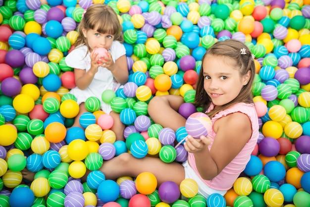 Rozochocone dzieci w pokoju zabaw z plastikowymi piłkami