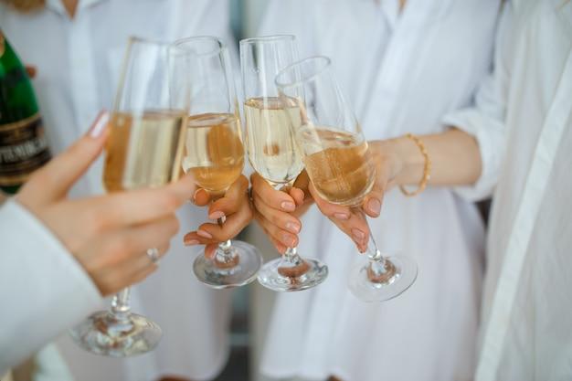 Rozochocone kobiety szczęk szkła szampan przy przyjęciem