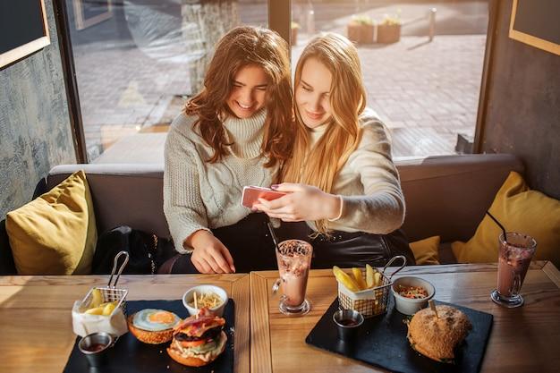 Rozochocone młode kobiety patrzeją telefon wpólnie. model blondynka trzyma go w rękach. patrzą i uśmiechają się. przy stole jest jedzenie. młode kobiety siedzą z boku przy stole.