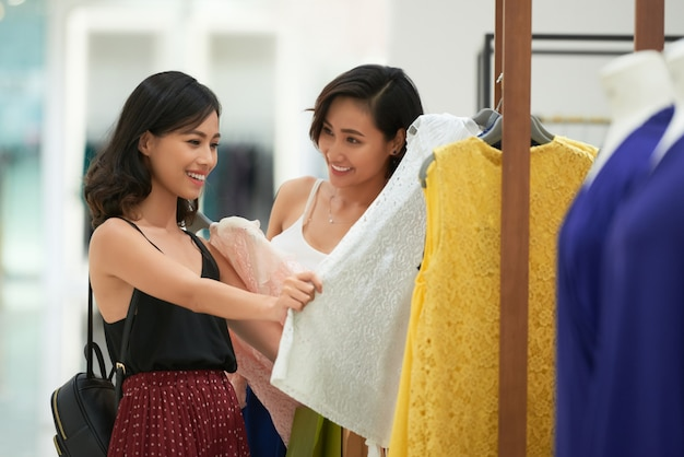 Rozochocone młode kobiety robi zakupy dla ubrań